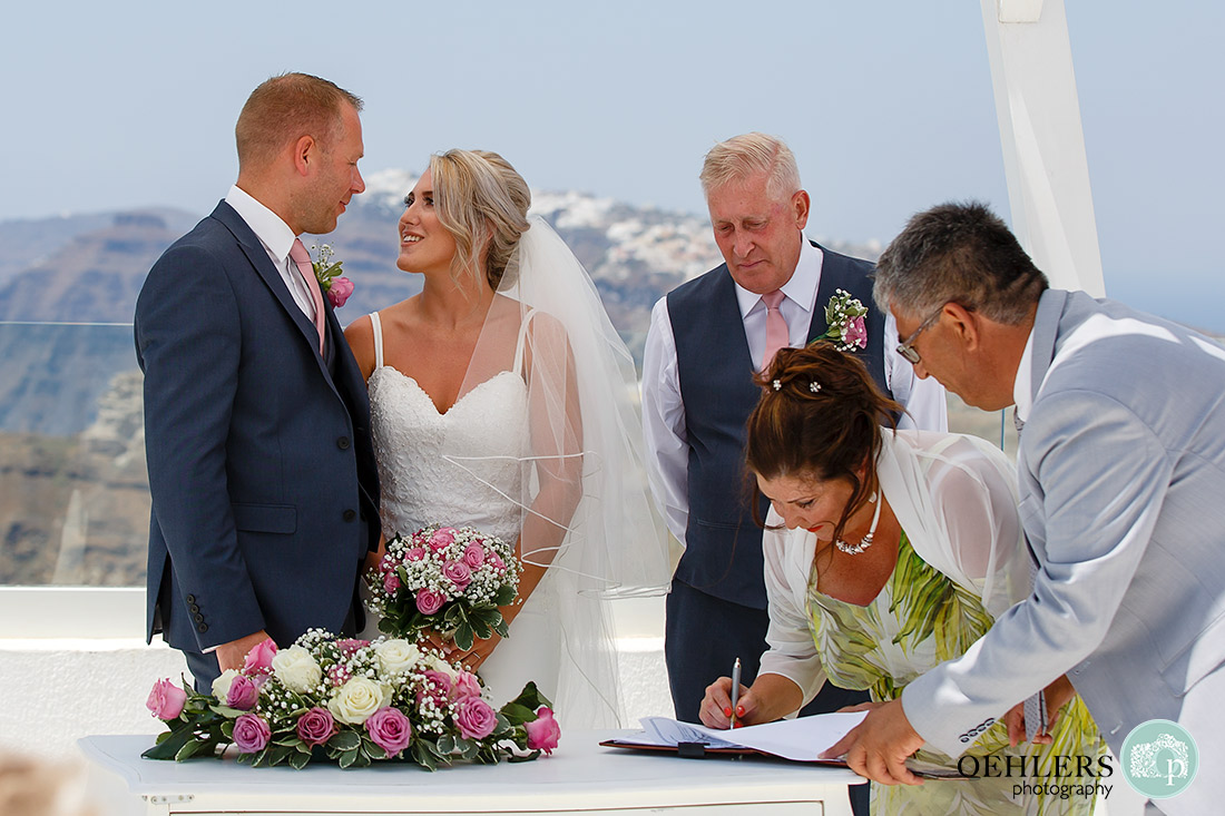 Mum witnessing the register whilst groom and bride look at each other and groom's dad looking over shoulder of mum.