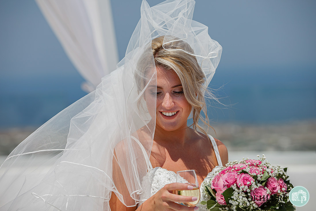 Santorini Destination Wedding Photographers - lovely, close-up photo of bride with champagne.