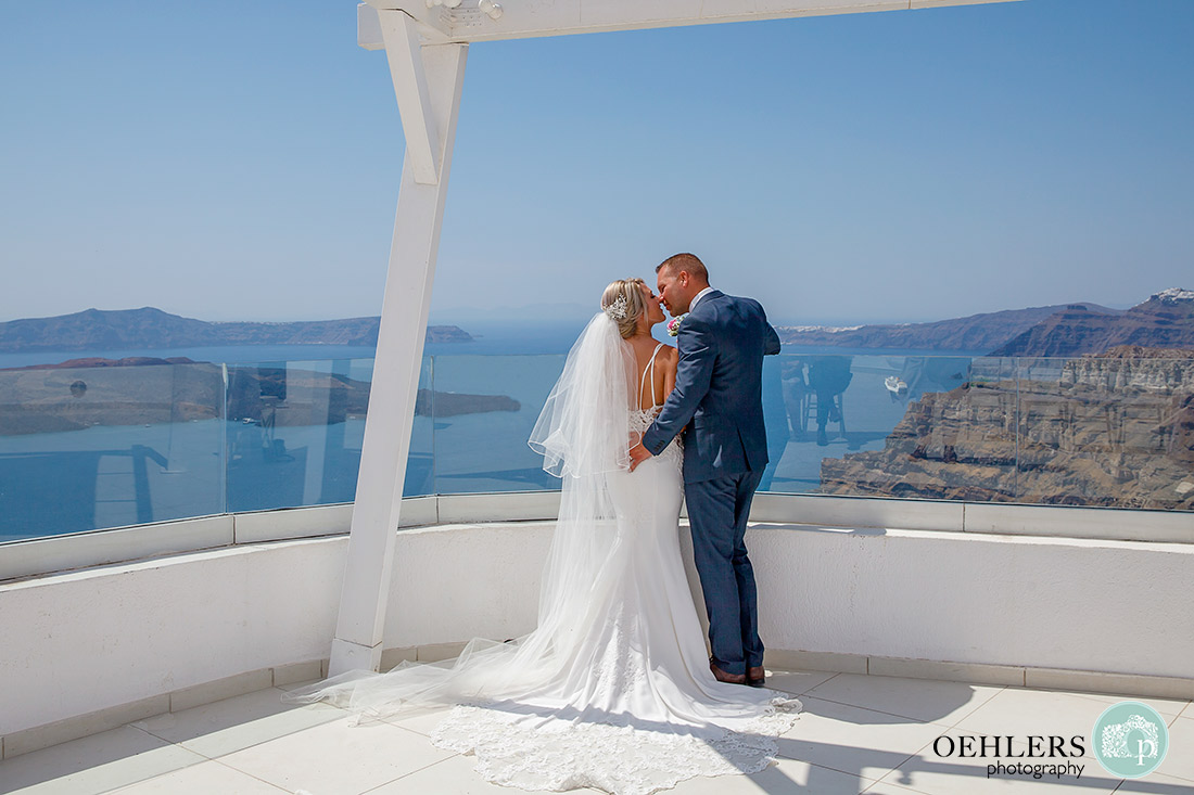 Santorini Destination Wedding Photographers - romantic photograph of bride and groom just about to kiss with beautiful backdrop.