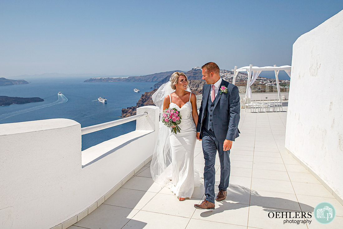 Bride and Groom walking hand in hand away from the ceremony area with backdrop of the Aegean Sea.