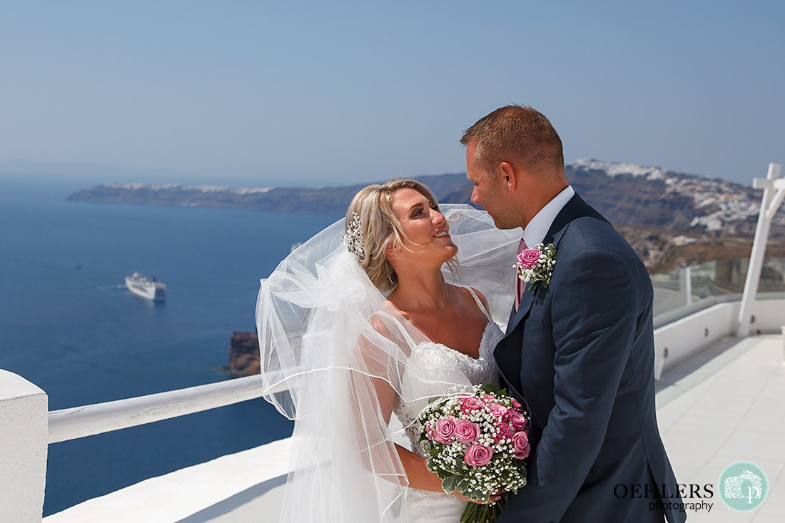 Destination Wedding Photographers - Santorini - bride and groom romantically looking into each others eyes.