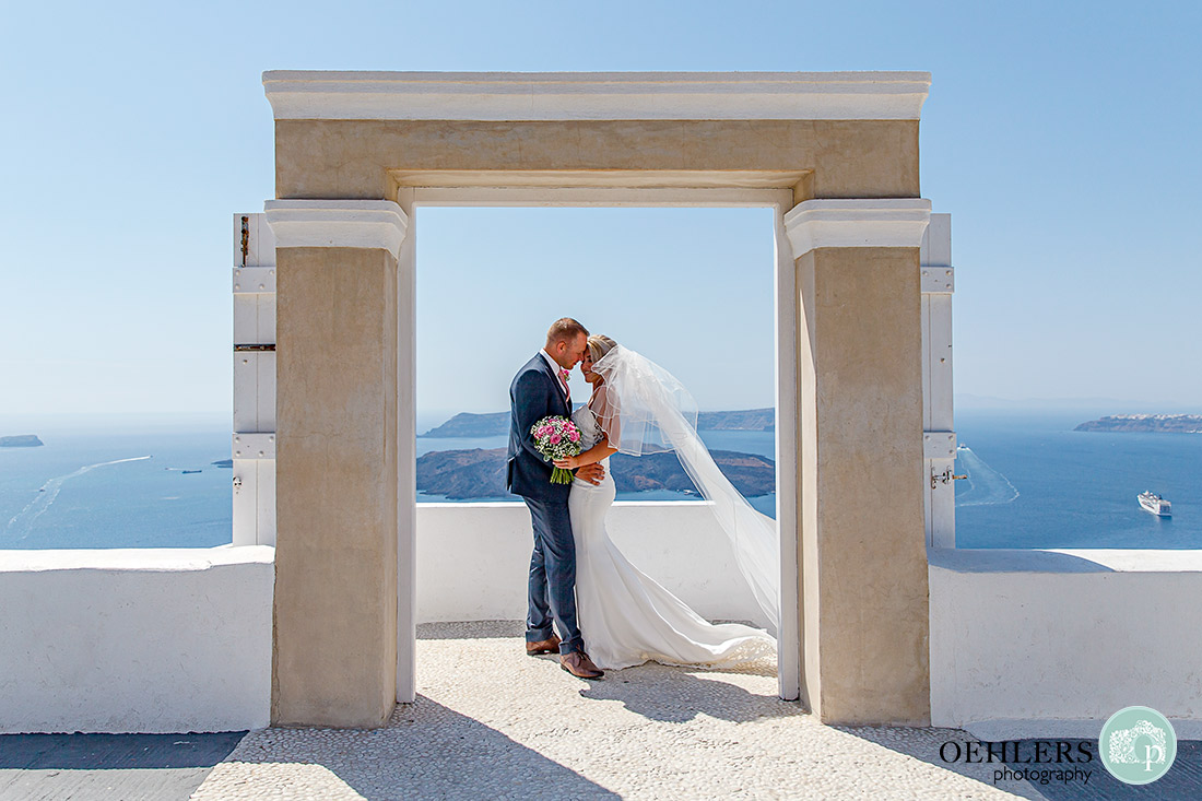 Destination Wedding Photographers - Santorini - bride and groom in a doorway with lovely view behind.
