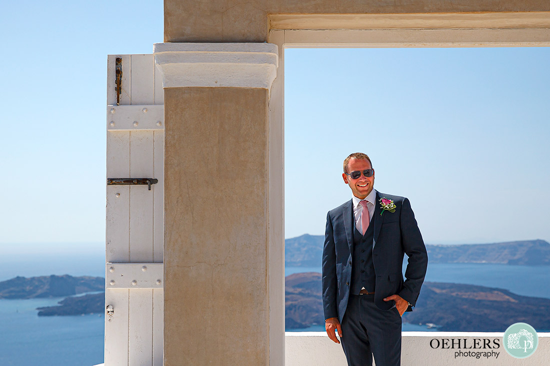 Cool groom posing in a doorway with great views behind.
