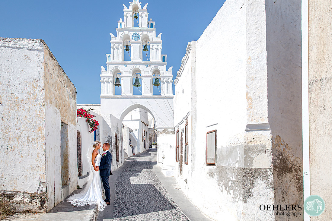 Romantic photograph of bride and groom in front of a bell tower in Megalochiri.