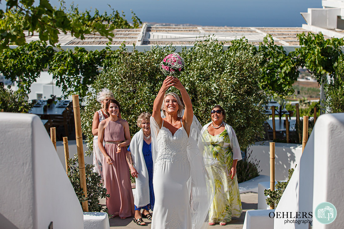Destination Wedding Photographers - Santorini - bride about to throw the wedding bouquet at Pyrgos Restaurant.