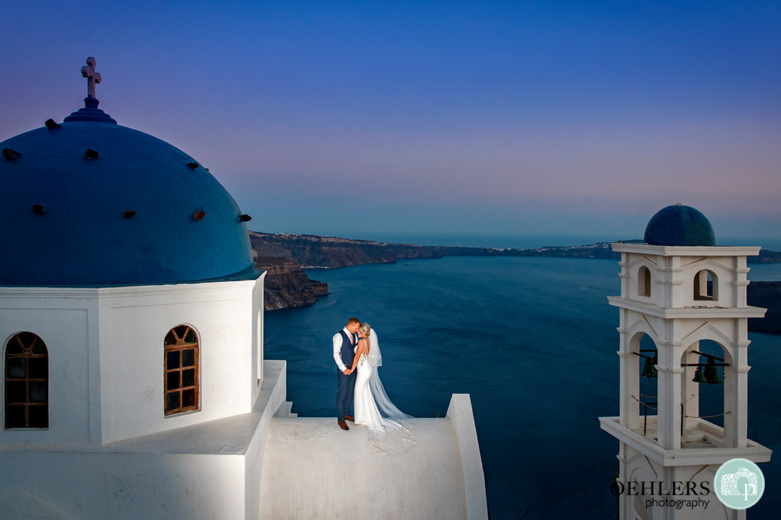 Destination Wedding Photographers - Santorini - bride and groom on top of a church in Imerovigli.
