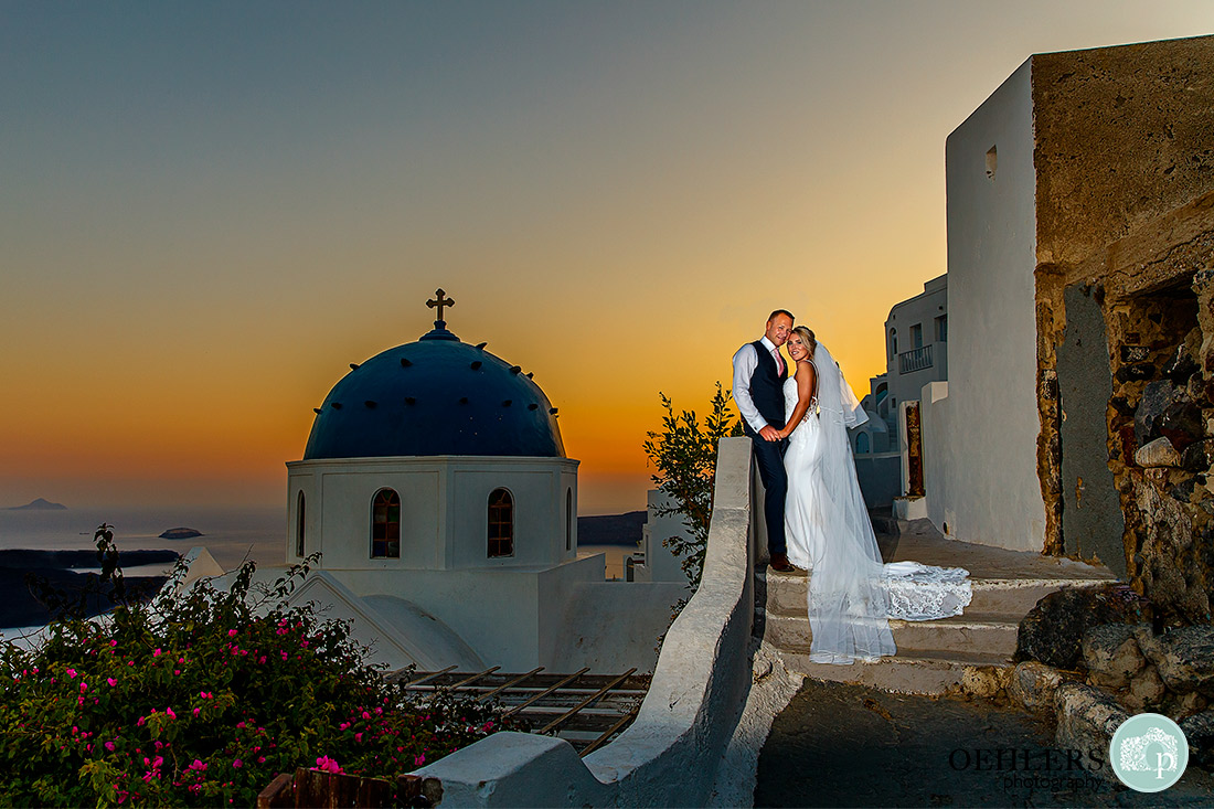 Beautiful sunset in the background with typical blue domed church in Imerovigli.