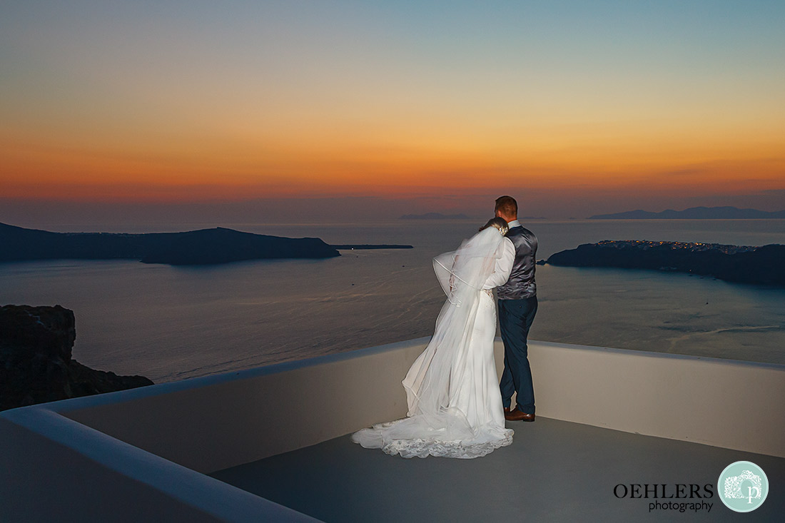 Bride and Groom on a roof top looking out to sea with the beautiful sunset.