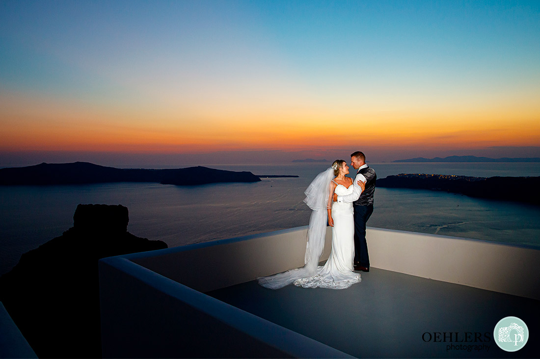 Destination Wedding Photographers - Santorini - bride and groom on a rooftop overlooking the sea with a beautiful sunset.