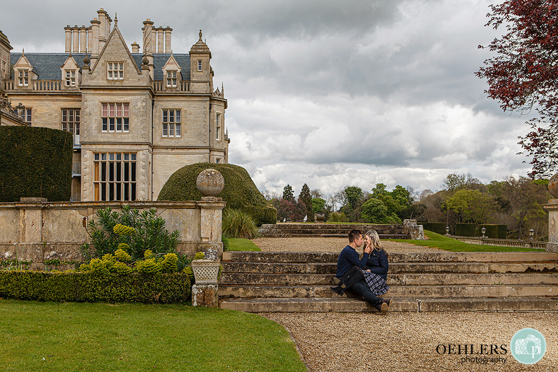 Stoke Rochford Wedding Photographer-Couple sitting on the steps in the grounds of Stoke Rochford Hall.