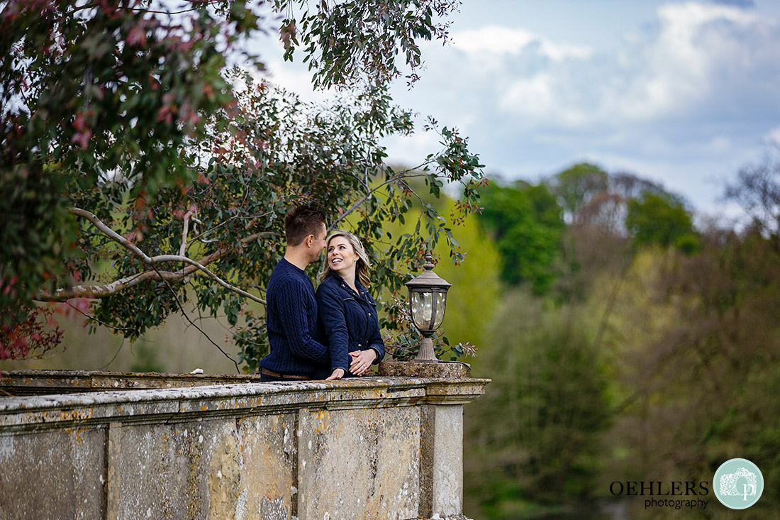 Couple standing at a corner of a wall with bride looking back at her groom.