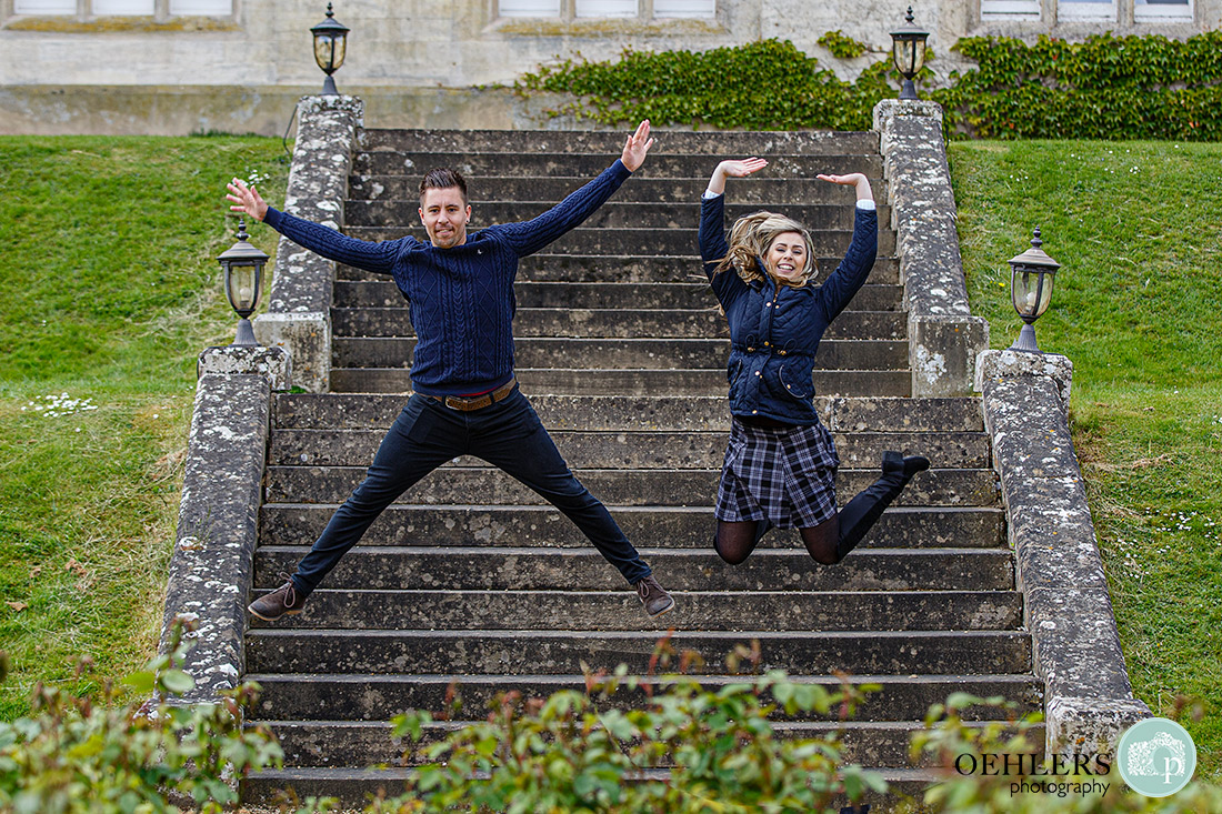 Nottingham wedding photographer - Couple jumping off steps and making shapes with their bodies.
