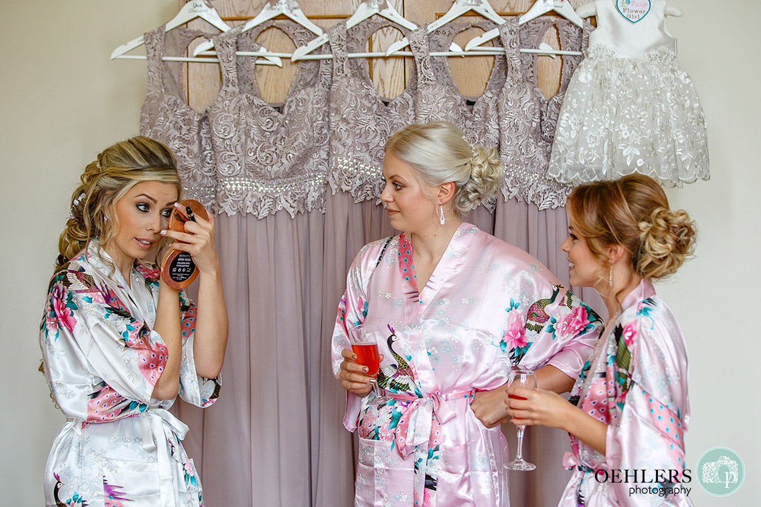 Bride finishing off her eye make up whilst bridesmaids look on.