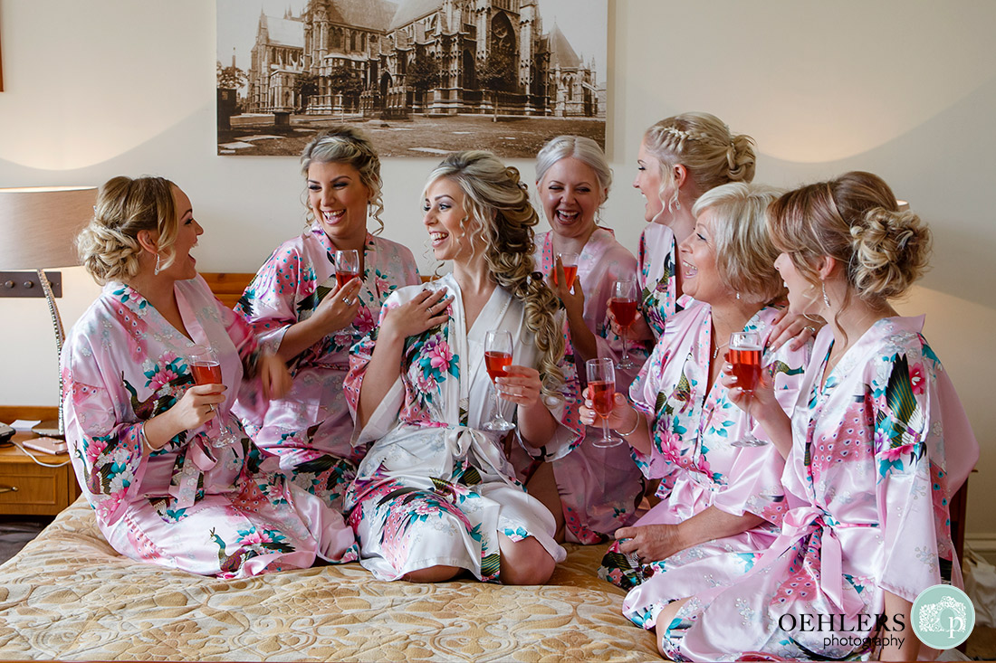 Bride and Bridesmaids and mum sitting on the bed chatting and sipping champagne.