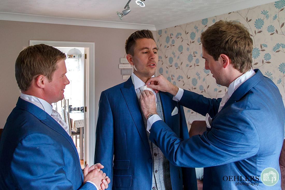 Groomsmen helping the groom get ready.