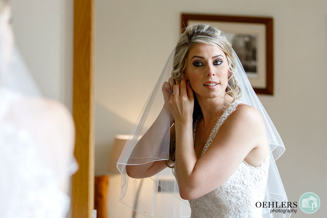 Reflection of the bride putting on her earrings in front of a mirror.