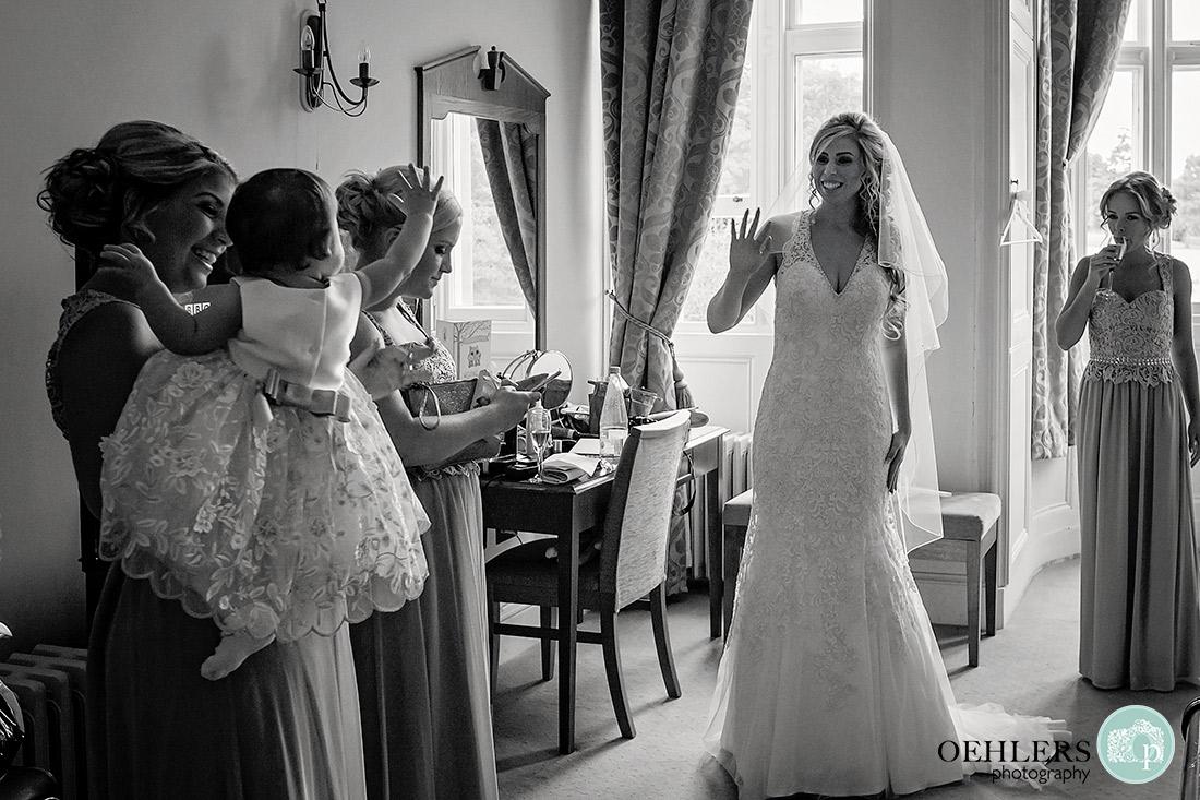 Bride waving at her flowergirl in the bridal suite.
