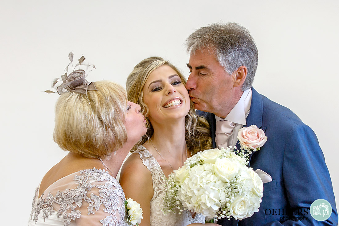 Stoke Rochford wedding PhotographyMum and Dad kissing the bride on both cheeks.