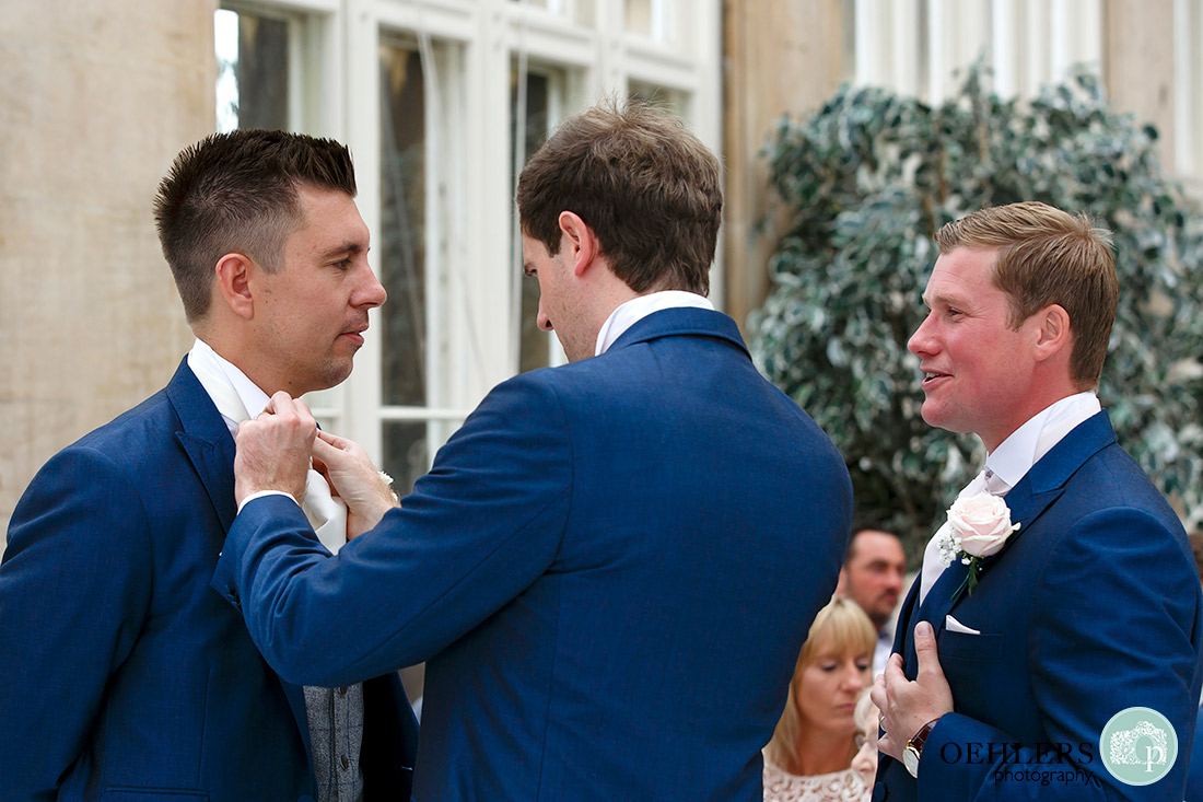 Nottingham wedding photographer - Groomsmen tidying up the groom before the bride enters.