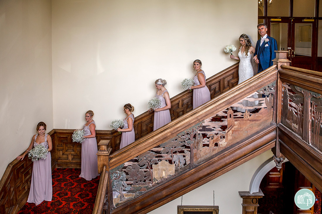 Bridal party and dad walking down the ornate staircase of Stoke Rochford Hall.