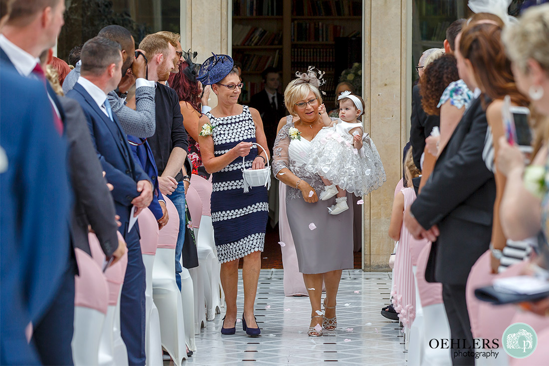 Both mums walking down the aisle with flower girl throwing the confetti.