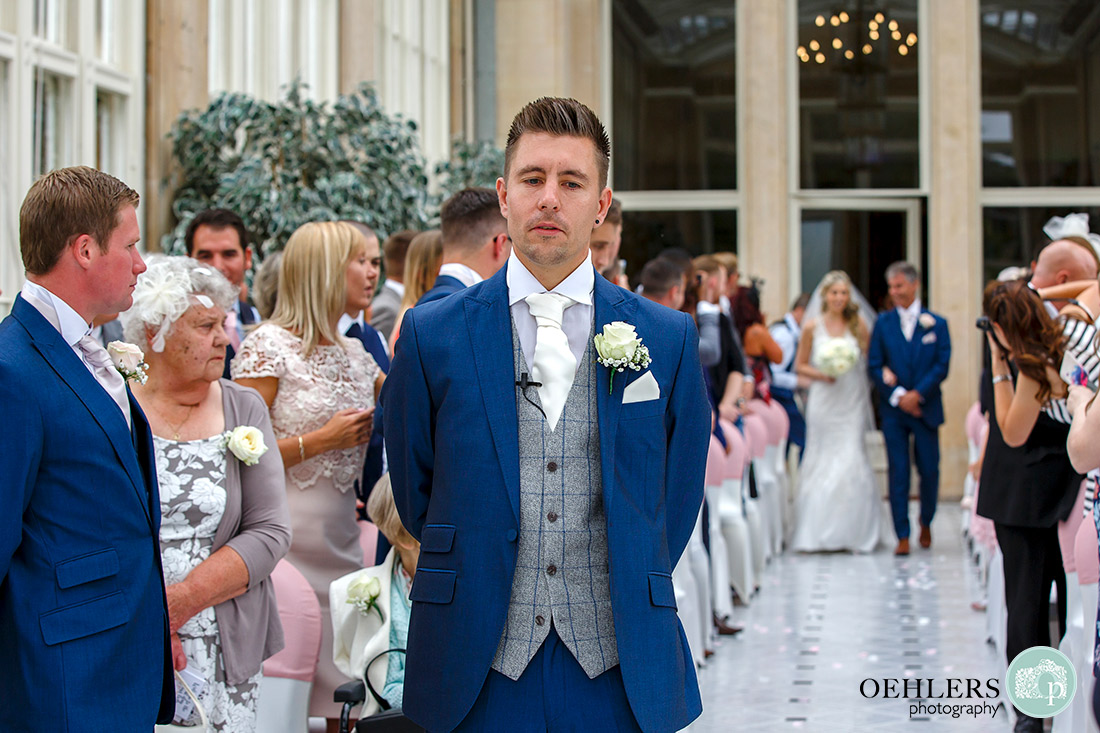 Groom waiting patiently with his back towards his bride as she walks down the aisle.
