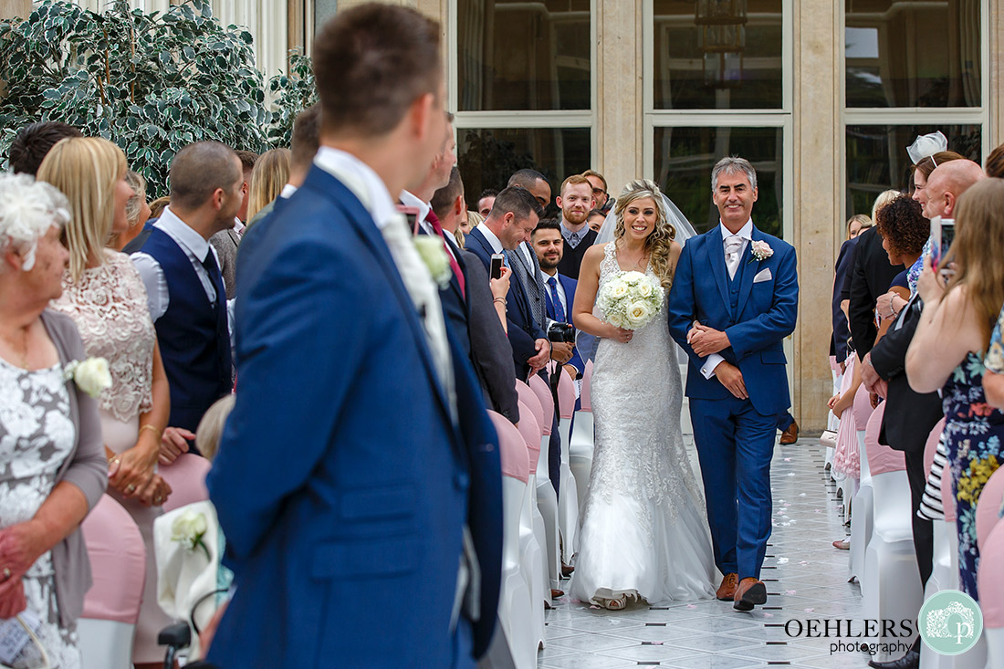 Stoke Rochford Wedding Photographer-Groom turns around to look at his bride as she smiles back at him.
