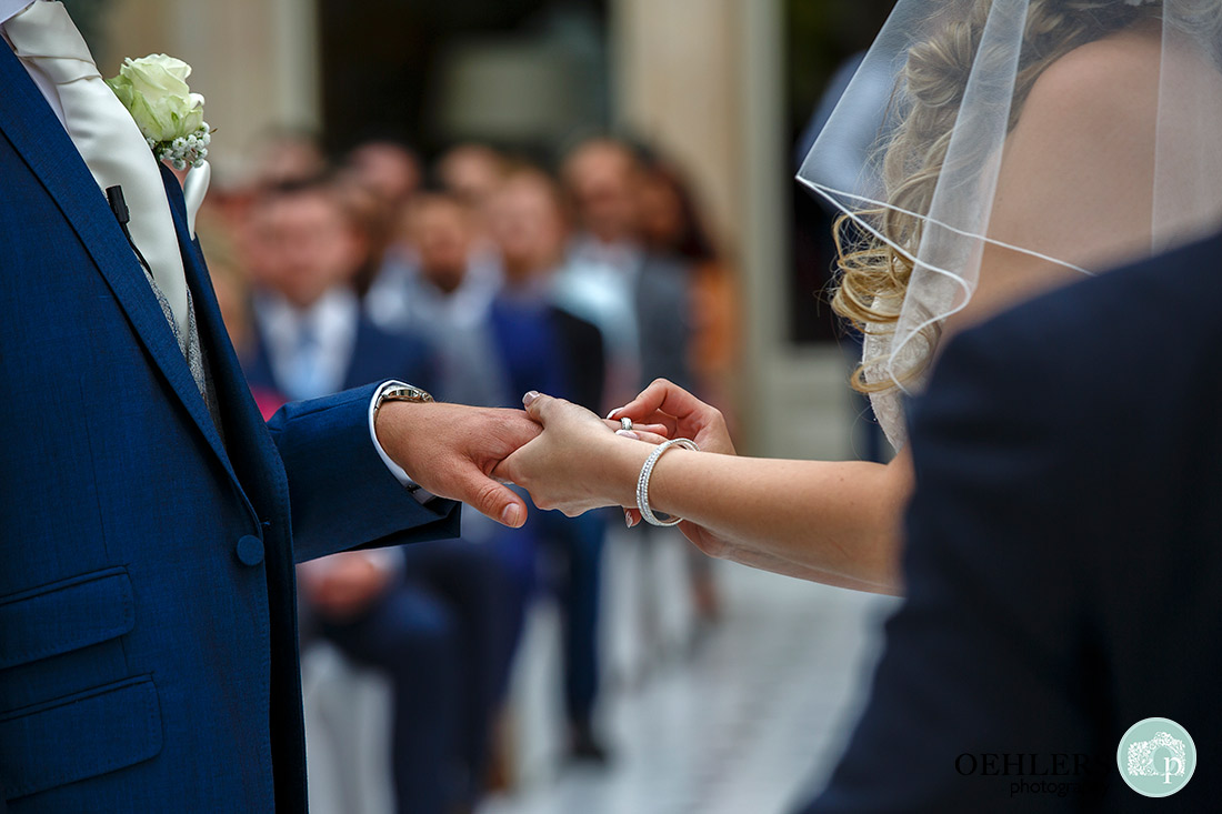 Stoke Rochford wedding PhotographyBride putting the ring onto her groom's finger.