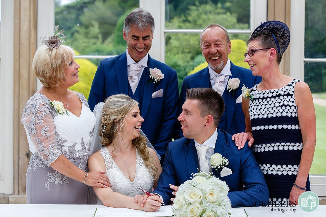 Bride and Groom with parents at the signing of the register laughing.