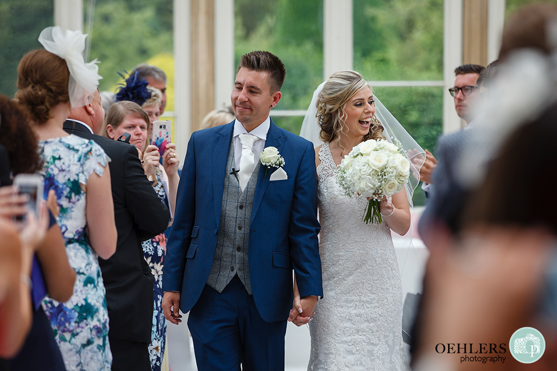 Proud groom walking his bride back up the aisle.