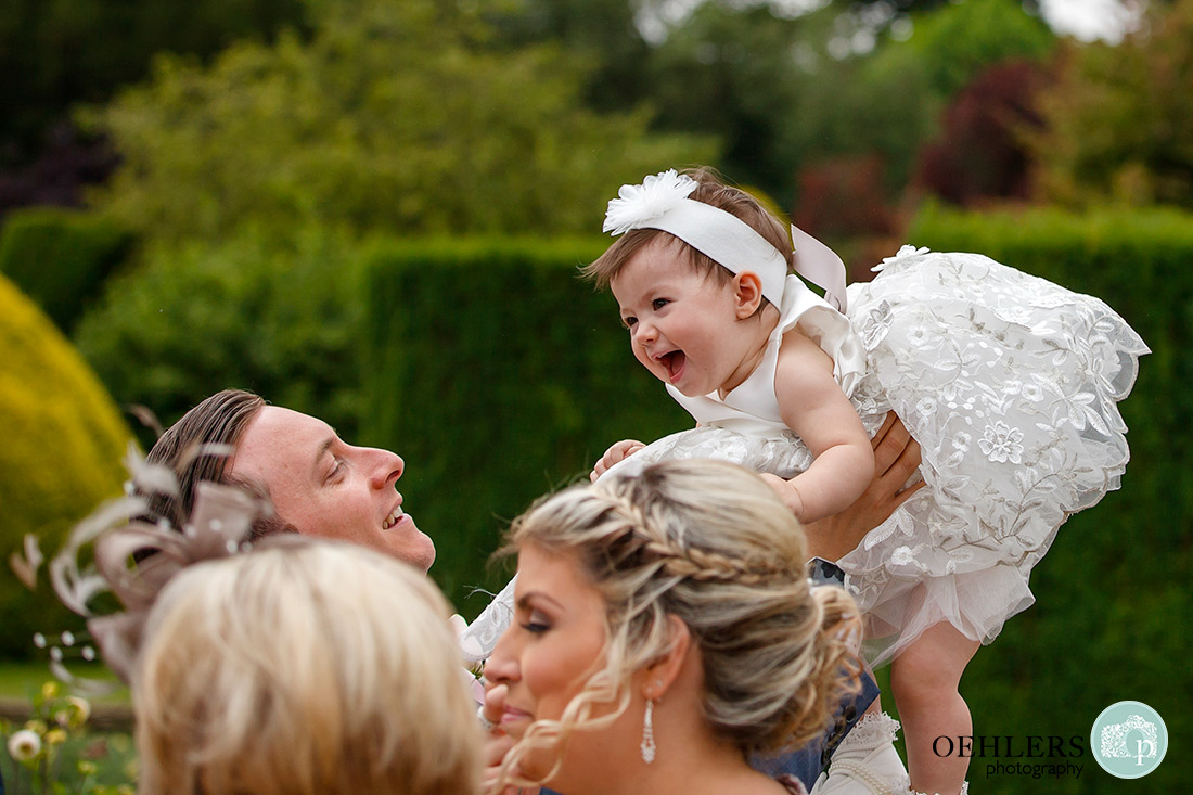 Stoke Rochford Wedding Photographer-Dad lifting the flower girl up.