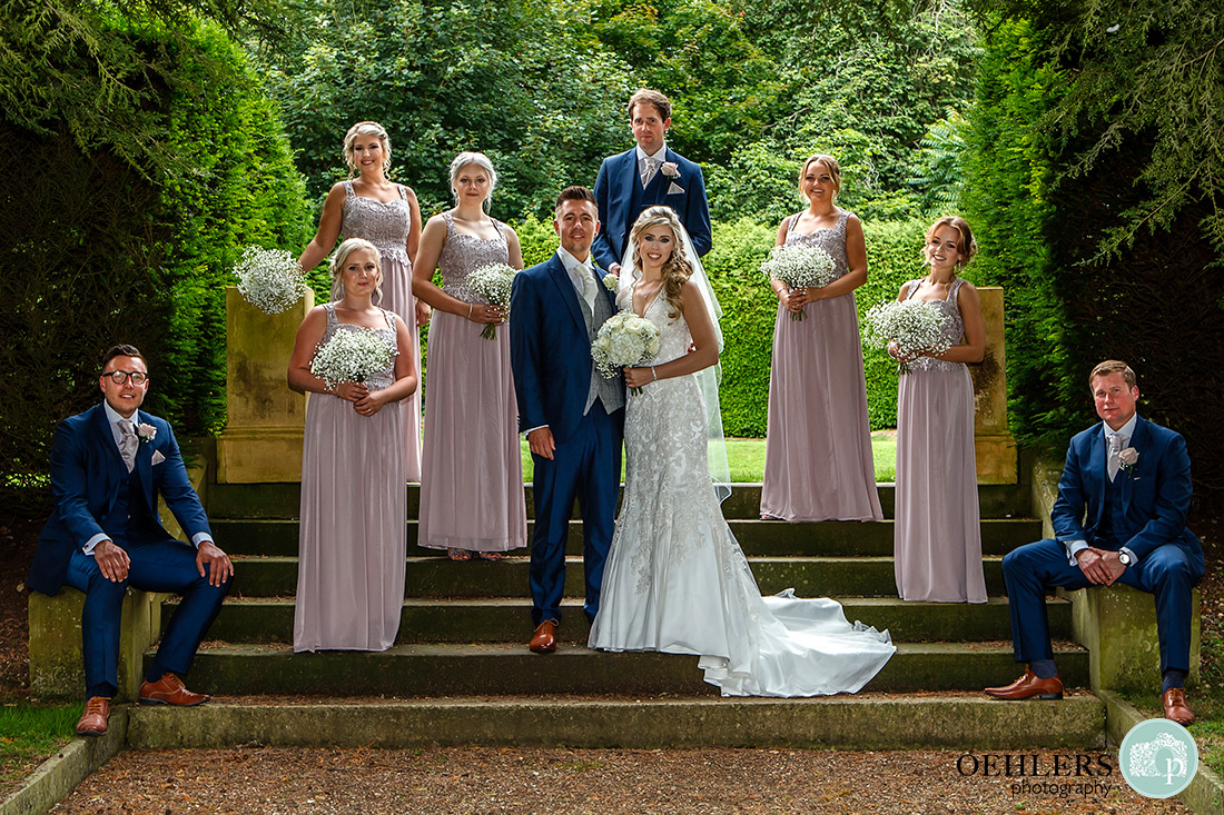 Stoke Rochford Wedding Photographer-Lovely photograph of the bridal party on the steps in the grounds of Stoke Rochford.