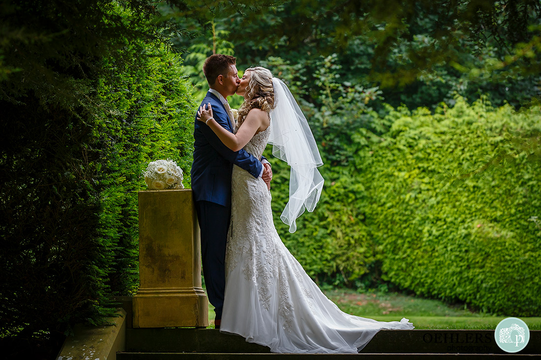 Bride and groom kissing on the top steps.