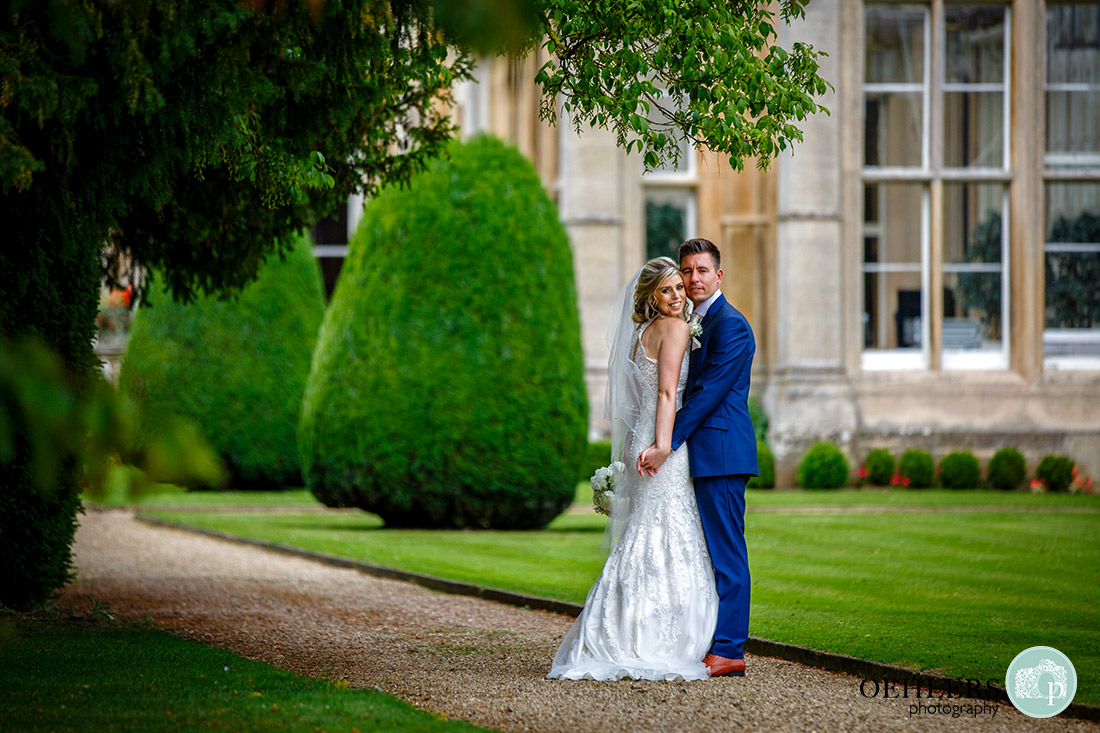Stoke Rochford Wedding Photographer-Bride and groom looking at the camera with the venue behind them.