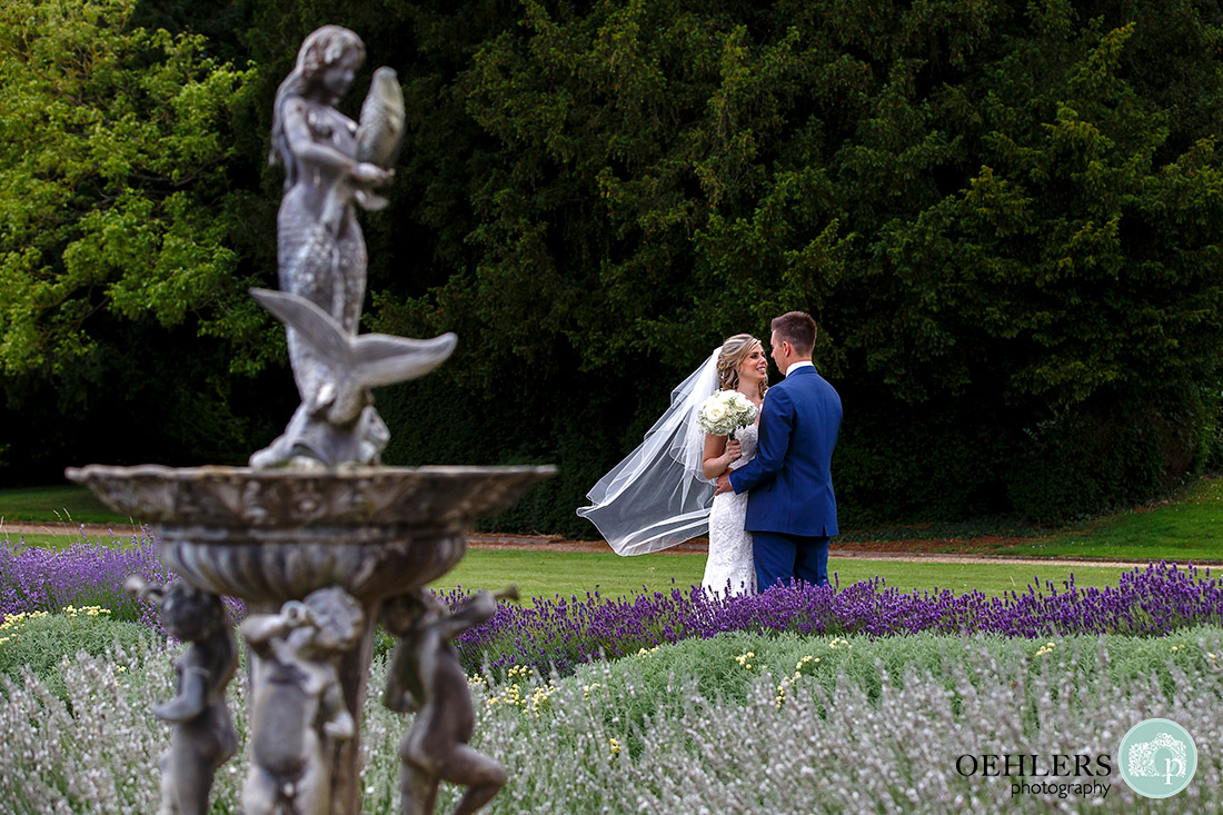 Bride and groom looking at each other in the fountain garden of the venue.