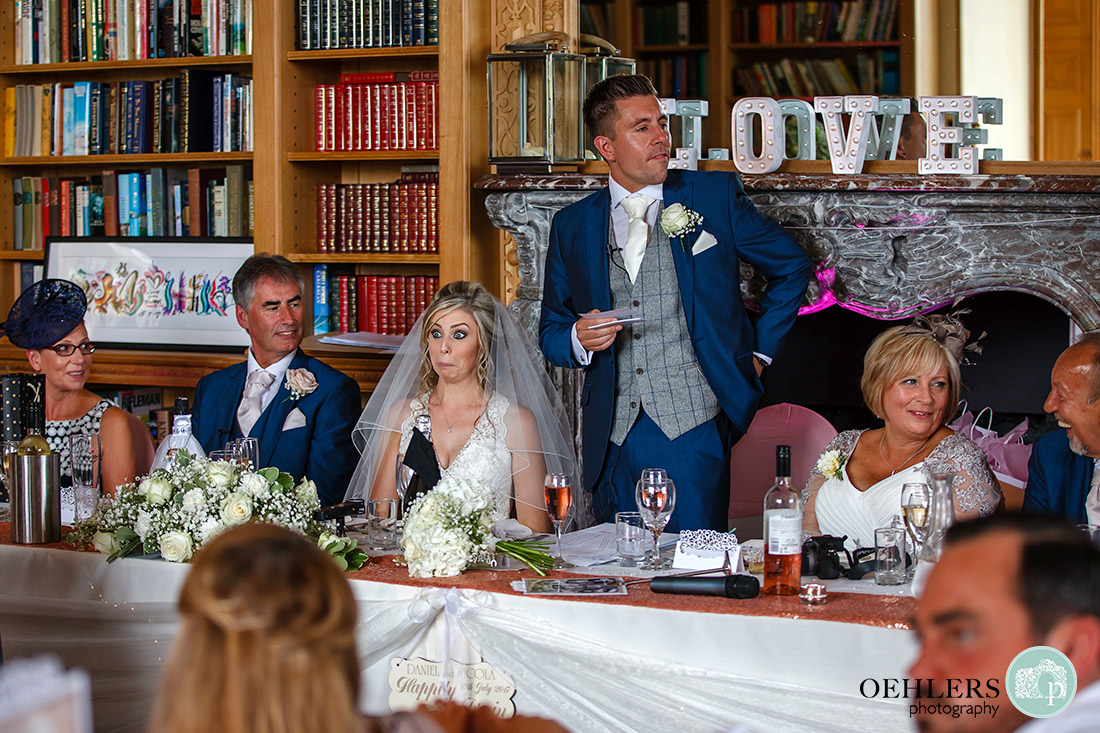 Groom making his speech at the top table with the bride pulling a face.
