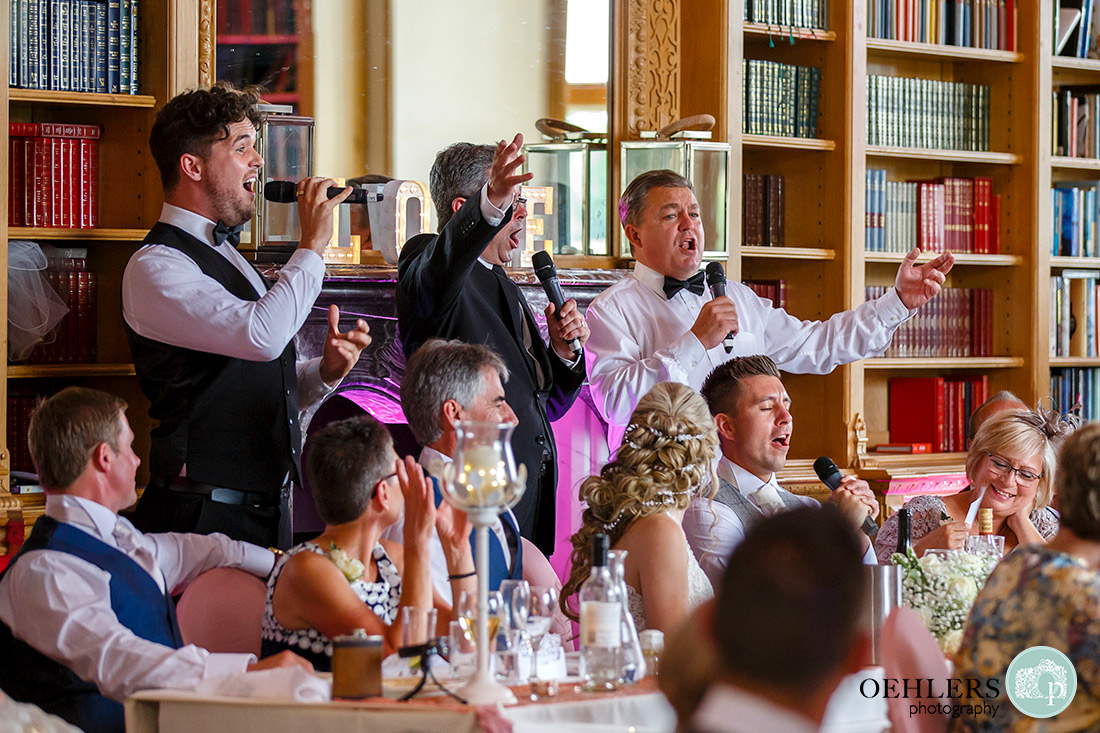 Stoke Rochford Wedding Photographer-All three singing waiters entertaining the top table.