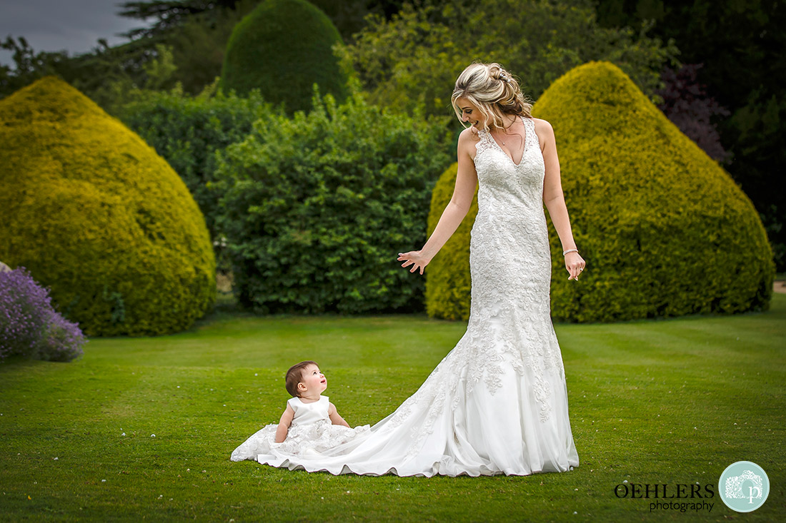 Stoke Rochford Wedding Photographer-Lovely photograph of the bride looking back at the flower girl sitting on her train looking at the bride.