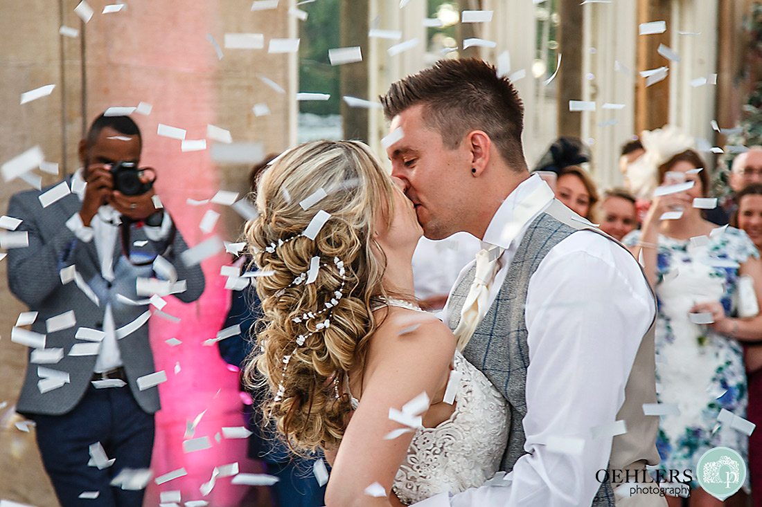 Close up of bride and groom kissing surrounded by confetti.