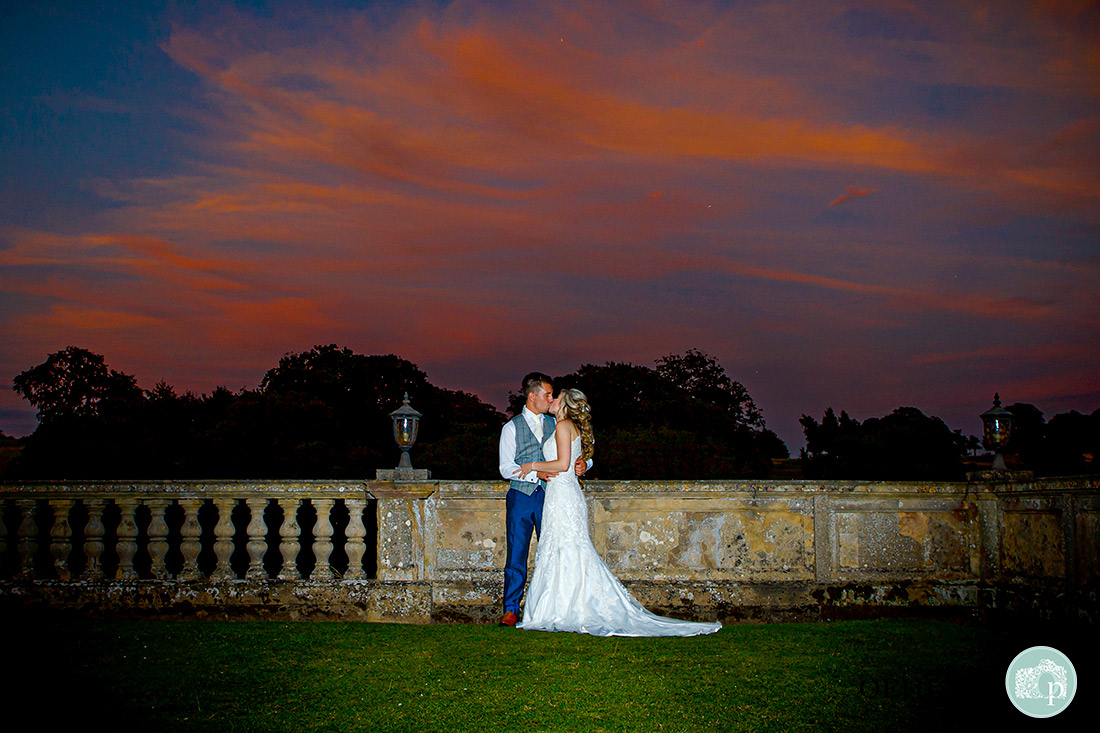 Stoke Rochford Photographer-Couple kissing in the grounds of the venue with a beautiful sunset.