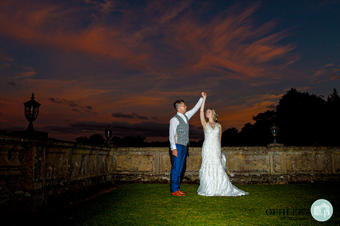 Couple practising their first dance in the grounds with the sunset behind them.