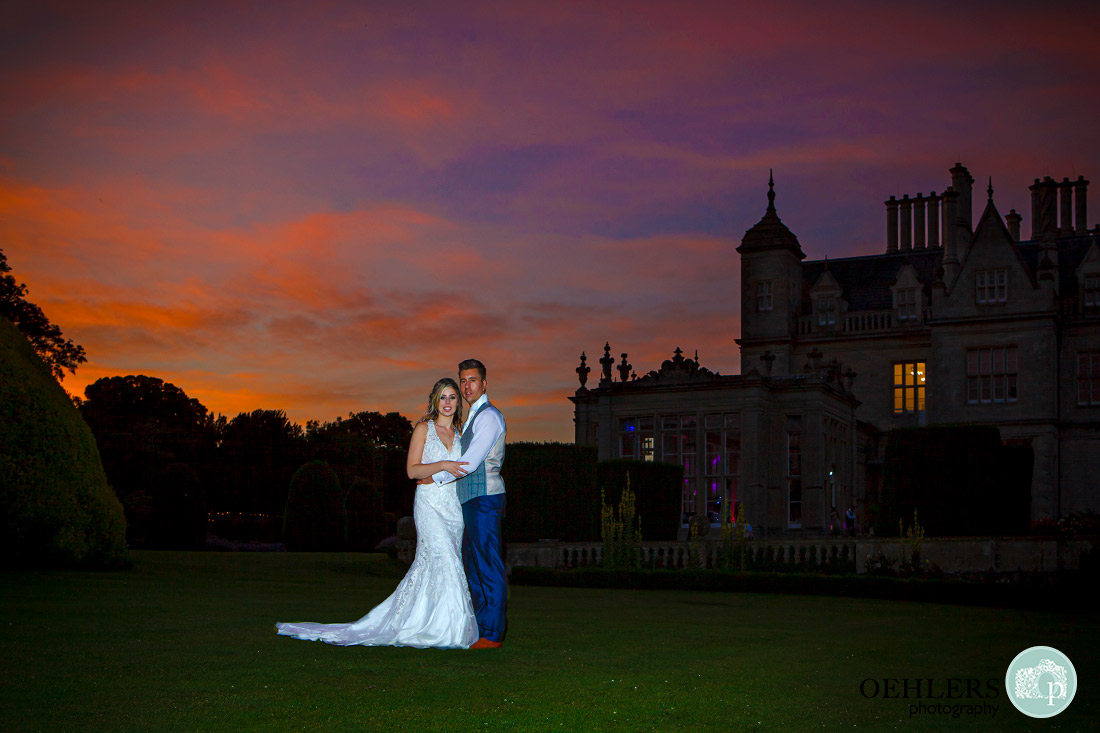 Stoke Rochford Photographer-Couple looking at the camera with the silhouette of Stoke Rochford behind them with a sunset sky.
