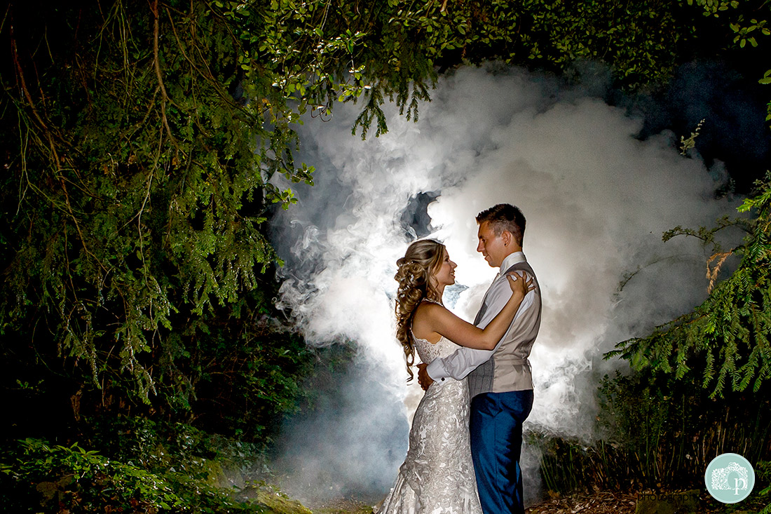Couple looking at each other with a smoke bomb lit in the background.