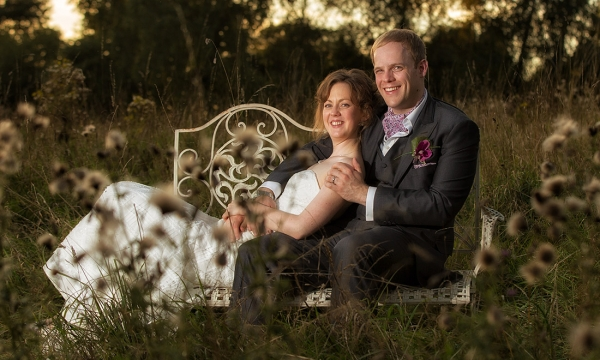 Bride and Groom sitting on a bench in the middle of a field.
