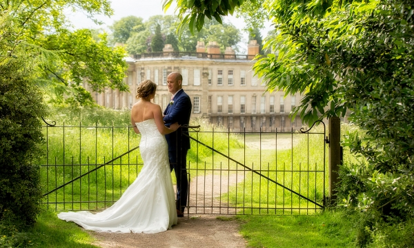 bride and groom in front of fascade of calke abbey