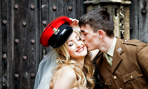 bride wears army cap whilst army grrom kisses her on the cheek
