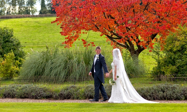 Groom and Bride walking with autumn leaves