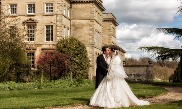 Groom and Bride kissing in front of Prestwold Hall