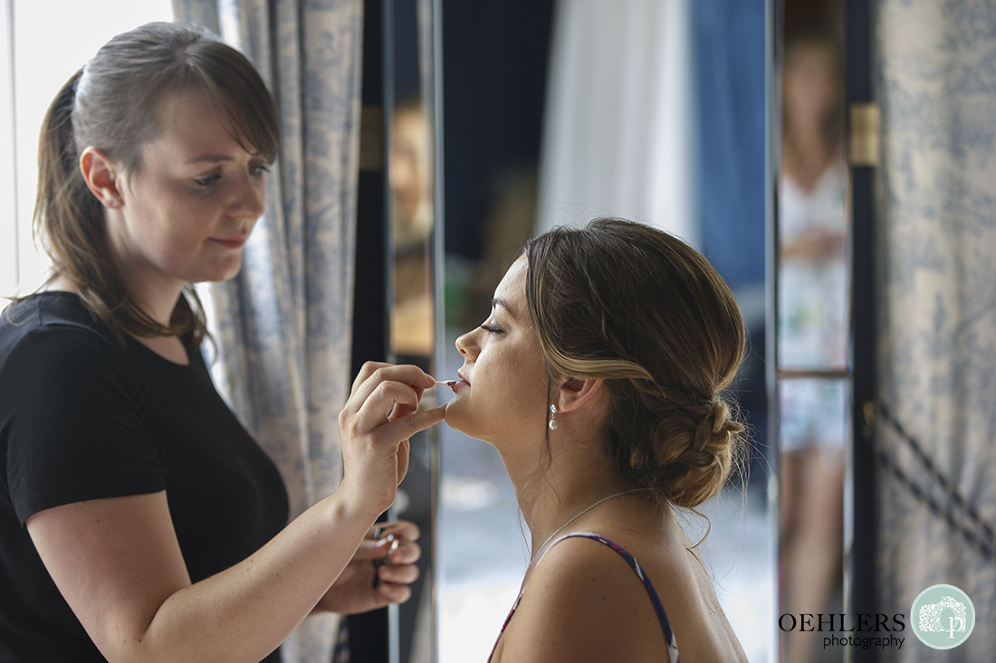 Bride having her lipstick put on her.