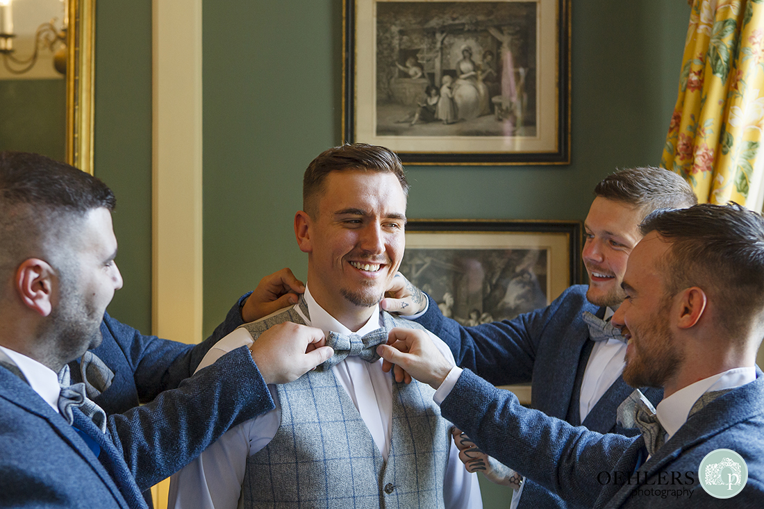 Prestwold Hall wedding photographer - Groomsmen having fun dressing the groom.